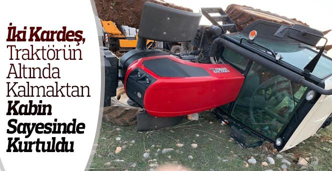 Kardeşler devrilen traktörden yara almadan kurtuldu.